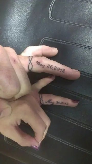 Infinity ring tattoos with a wedding date done on the side of your fingers