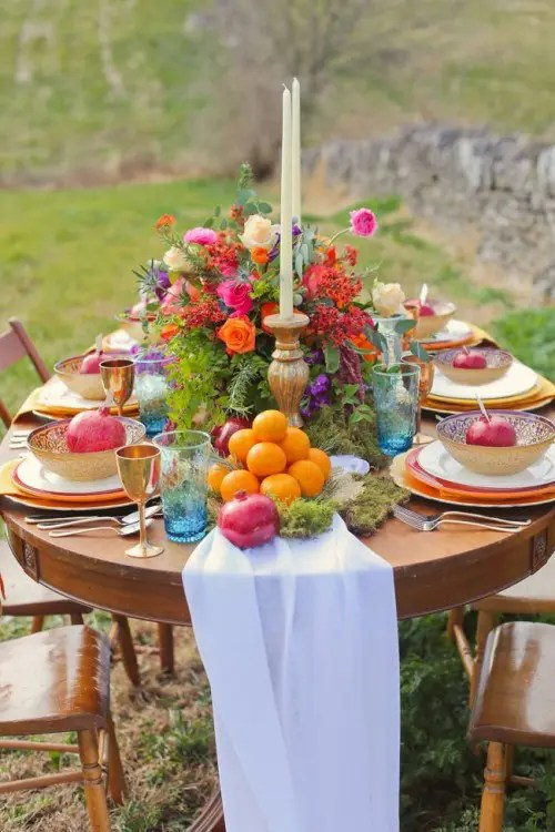 a bright tablescape with a white runner, moss, fruits, a colorful floral centerpiece and gold bowls