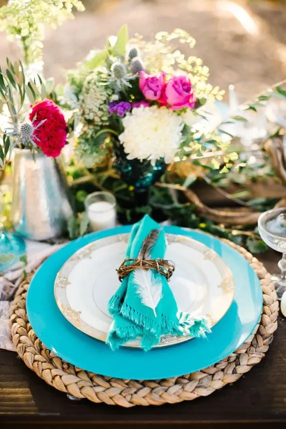 Picture Of a colorful tablescape with turquoise plates a wicker charger bright florals in