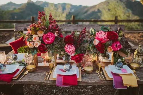 a lush and colorful tablescape with bright florals, textiles, gilded touches and candle lanterns