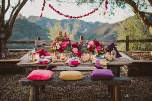 a bright boho tablescape with colorful pillows and florals, gilded touches, candle lanterns and garlands
