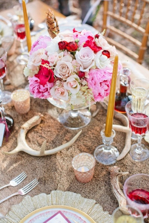 a faux fur tablecloth, antlers, gold chargers, candles, bright florals and colored glasses