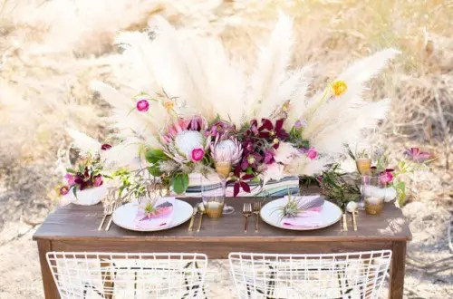 a boho chic table setting with bright florals and pampas grass, tie dye napkins and candles