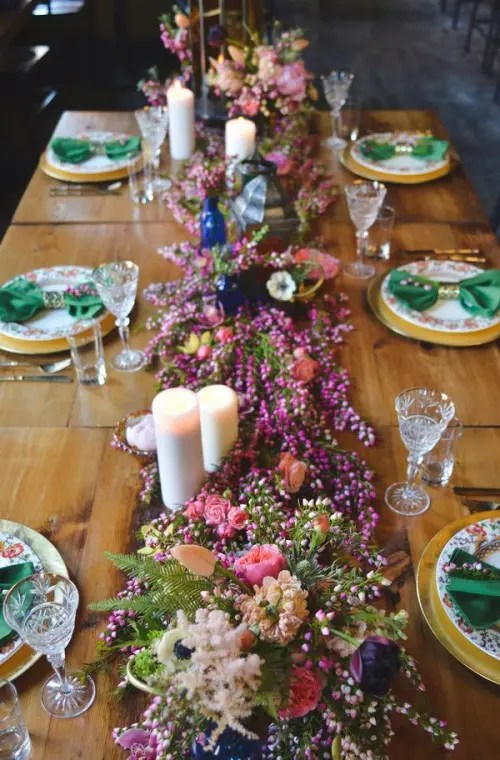 a bright table setting with a colorful floral table runner, floral print plates and emerald napkins plus candles