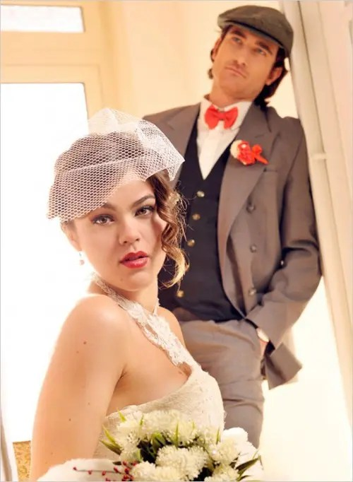 a vintage groom's outfit with a taupe suit, a graphite grey waistcoat, a white button down, a red bow tie and a cap