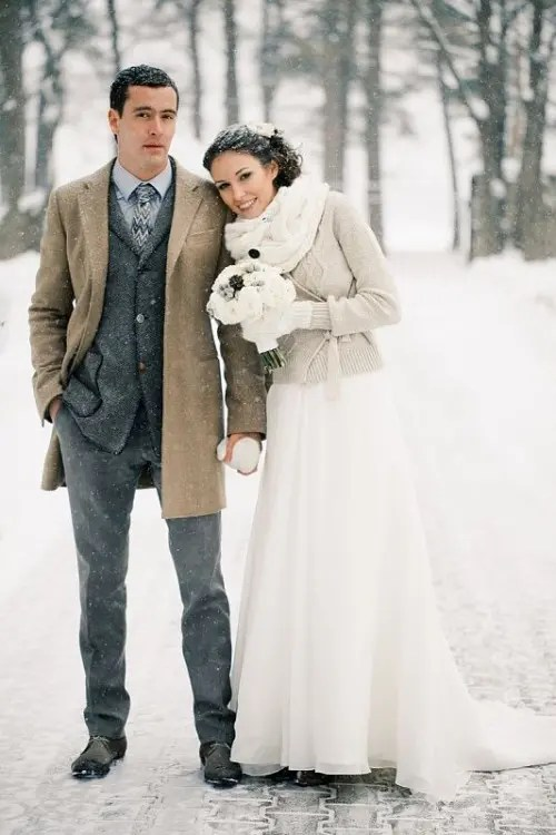 a grey tweed suit, a grey button down and a printed tie plus a beige coat for a snowy wedding day