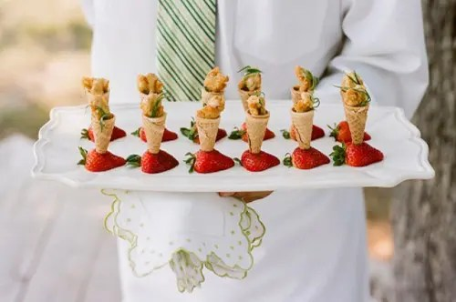 fried chicken in ice cream cones placed into strawberries looks very unusual
