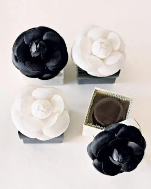 boxes with black and white fabric blooms on top for wedding favors