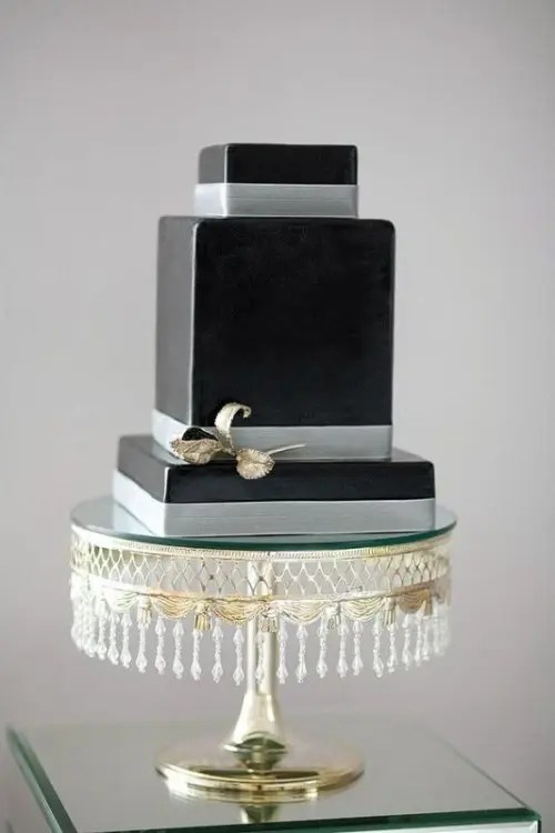 a black square wedding cake with silver ribbons and a touch of metallics