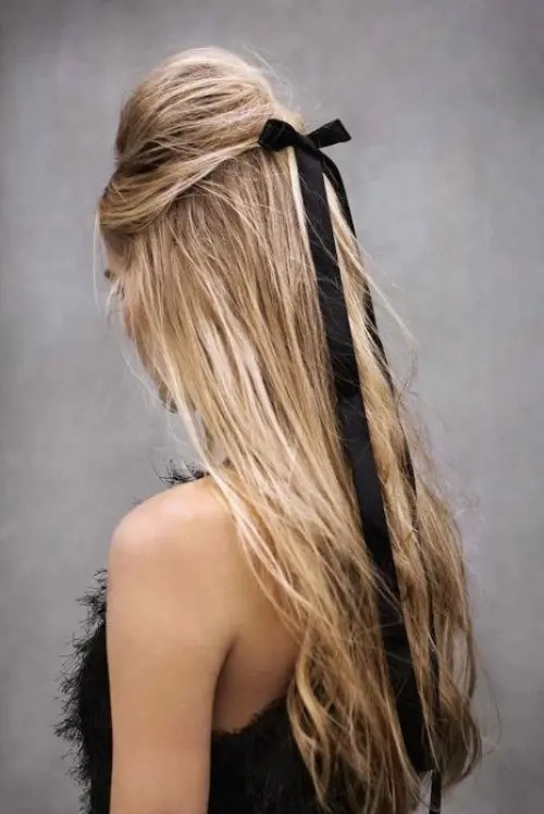a half updo with a bump accented with a black ribbon bow instead of blooms