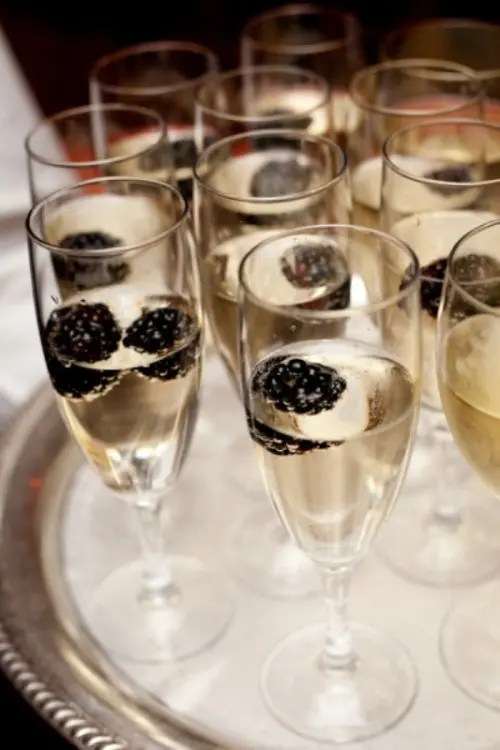 sparkly wine plus blackberries is a cool idea of a signature drink for your wedding