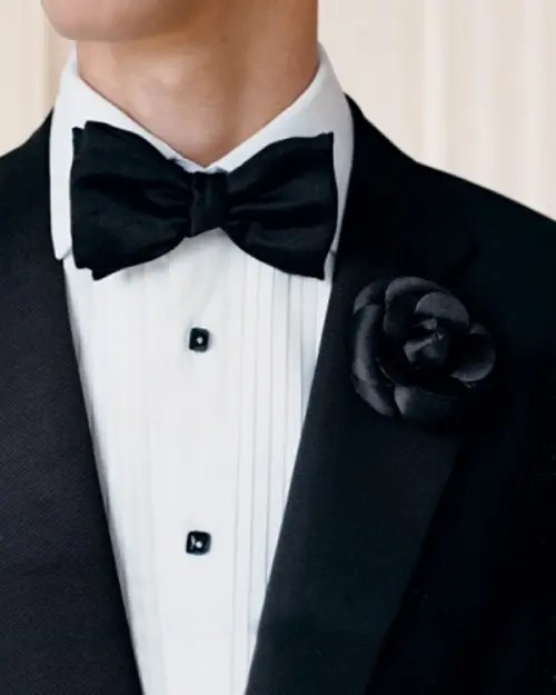 a black tux with a black fabric flower boutonniere for a soft gothic groom