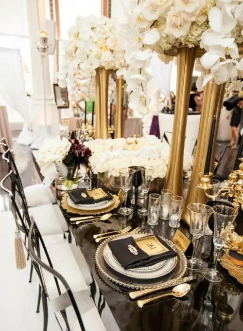 a black and gold wedding tablescape with tall gold vases, black and gold settings and white rose centerpieces