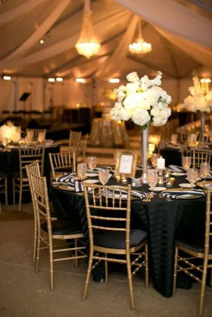 a black, white and gold wedding tablescape with striped napkins, a lush white bloom centerpiece, white candles and a gold frame