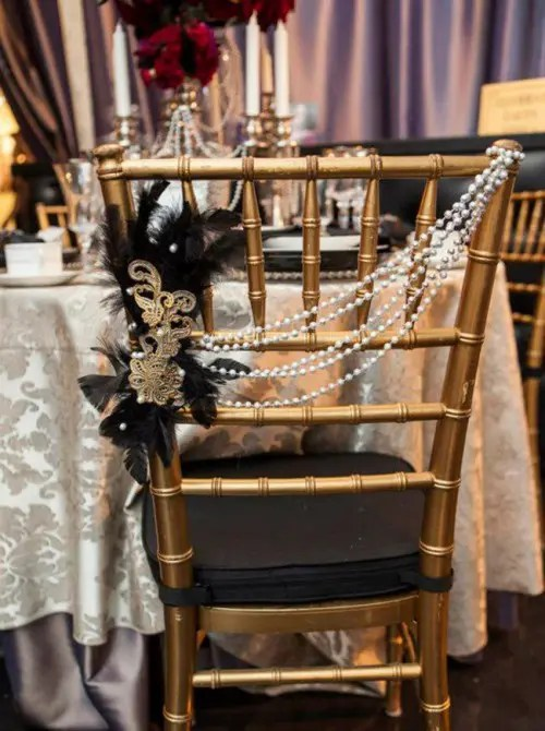 a black chair with beads, faethers, lace and brooches