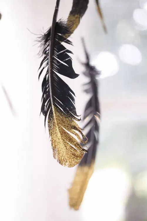 black and gold feathers will be a fun decor idea for such a wedding