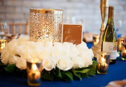 9090f639 a navy, white and gold wedding table setting with lush blooms, candle  holders and