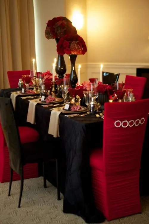 a red and black wedding tablescape with a black tablecloth, black and red chairs, black vases with red roses