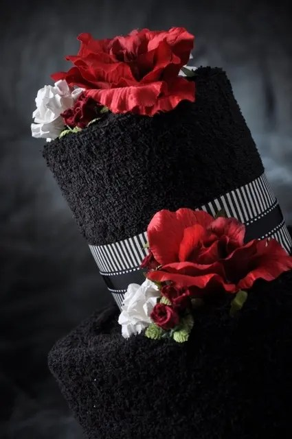 a black wedding cake with hot red and white flowers plus ribbons