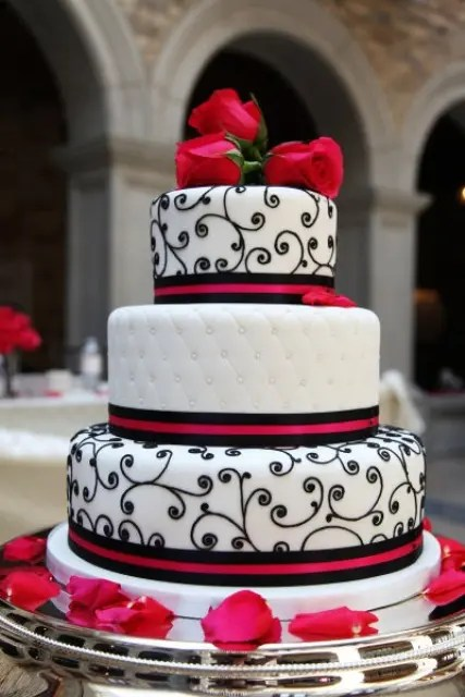 a black and white wedding cake with various patterns and touches of red and red roses