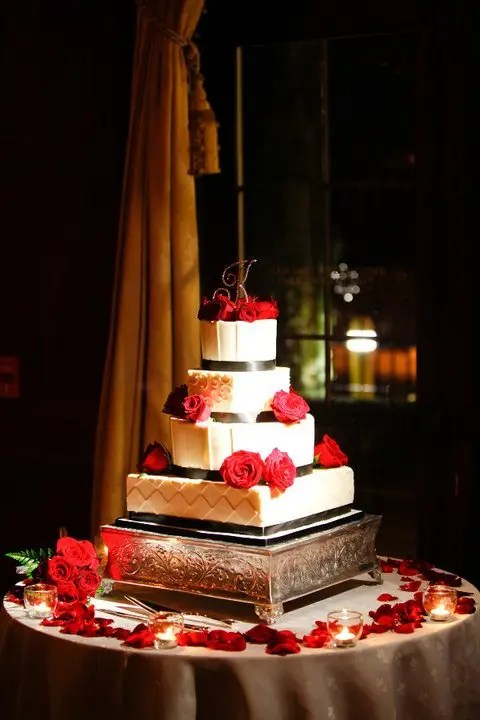 a white wedding cake decorated with black ribbons and red roses on top