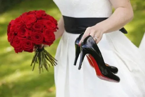 black shoes with red bottoms and a red rose bouquet and a black sash for the bride