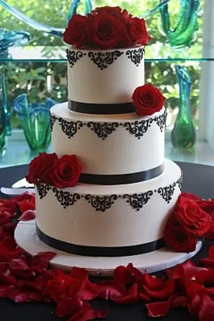a black and white wedding cake topped with red roses served on red petals is a chic idea