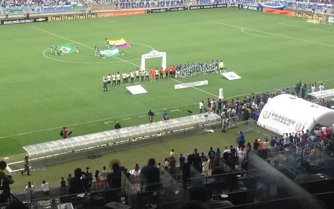 Jogadores de Cruzeiro e Corinthians antes do jogo; ao fundo bandeiras em homenagem à Chape. Foto: Reprodução