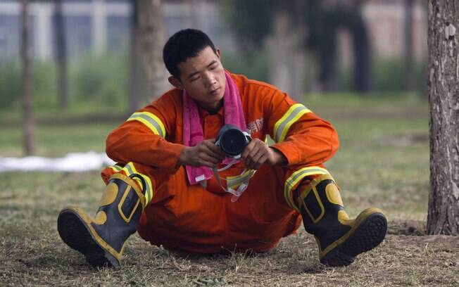 Bombeiro chinês ajusta sua máscara enquanto espera para começar a atuar em área atingida por explosões em Tianjin, China