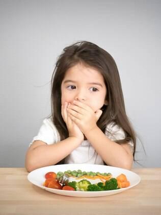 criança tampando a boca para comer