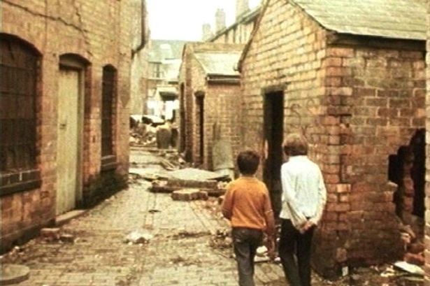Two boys walking between buildings waiting to be demolished.