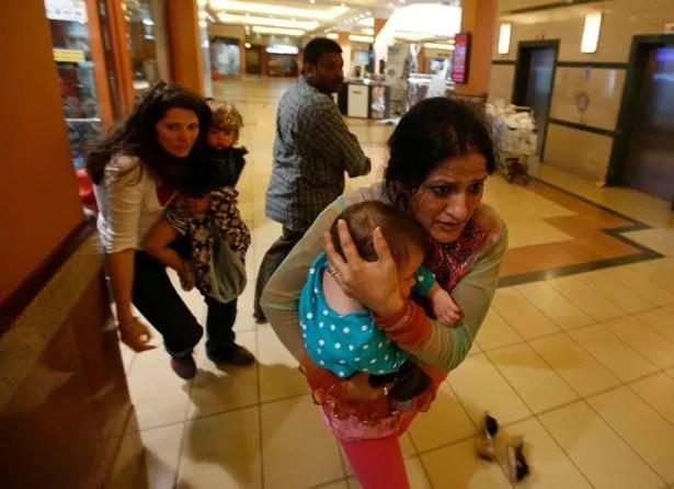 Women run for safety as armed police hunt gunmen during the 2013 massacre