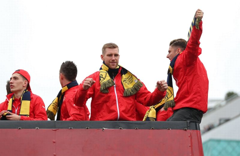 Per Mertesacker and Olivier Giroud celebrate during the parade