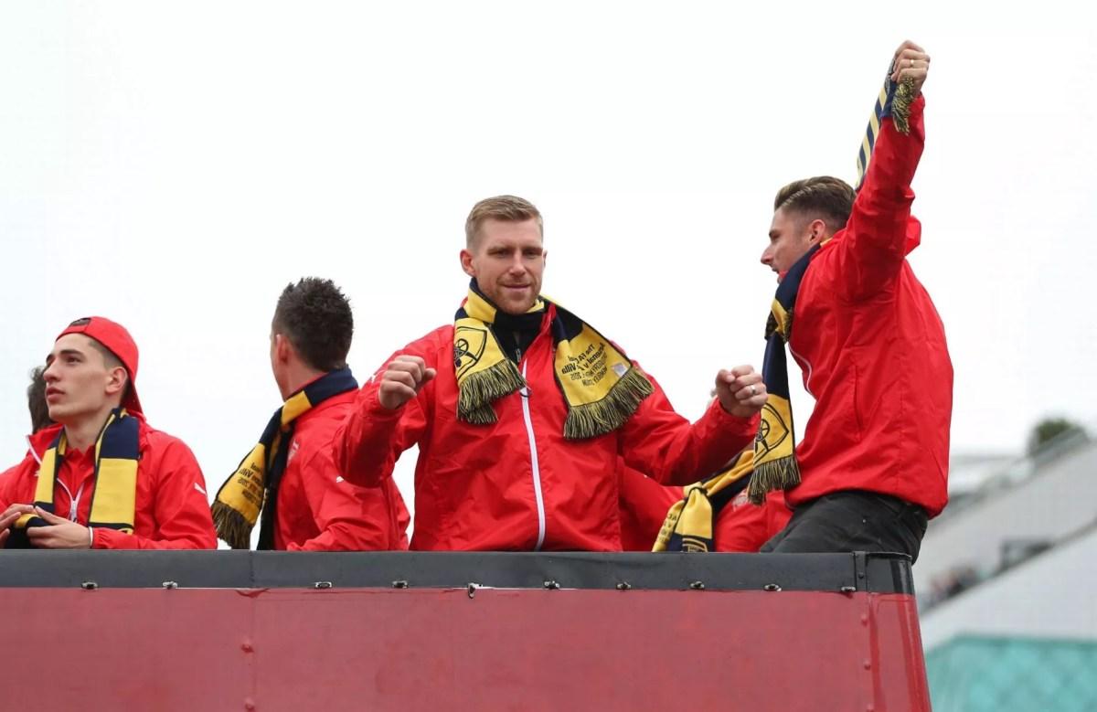 Per Mertesacker and Olivier Giroud celebrate during the parade