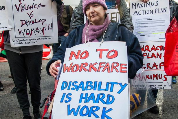Hundreds of disabled activists protest outside the headquarters of Maximus