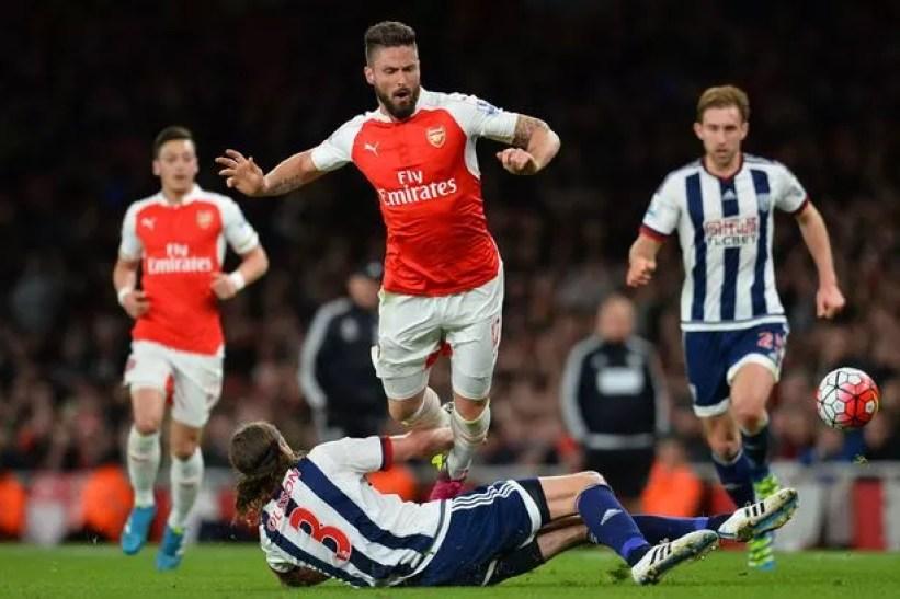 West Bromwich Albion's Swedish defender Jonas Olsson (floor) tackles Arsenal's Welsh midfielder Aaron Ramsey