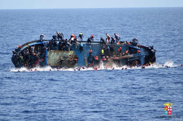 This handout picture released on May 25, 2016 by the Italian Navy (Marina Militare) shows the shipwreck of an overcrowded boat of migrants off the Libyan coast today.
