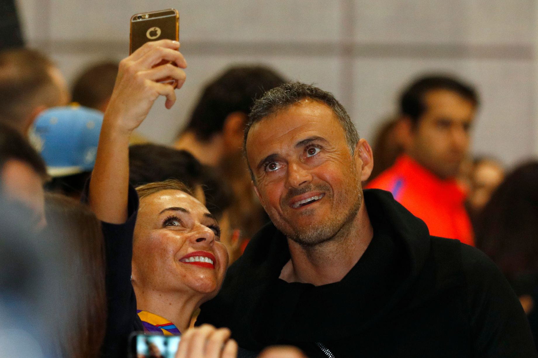 Luis Enrique poses for a photo with a fan as he arrives at Manchester Airport