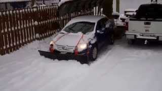 Nordic V-Plow on a Gravel Driveway Pushed by a Small Car