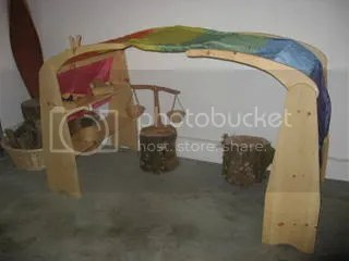 A classic Waldorf playspace - covered with a rainbow silk. I think the stands can be made easily.