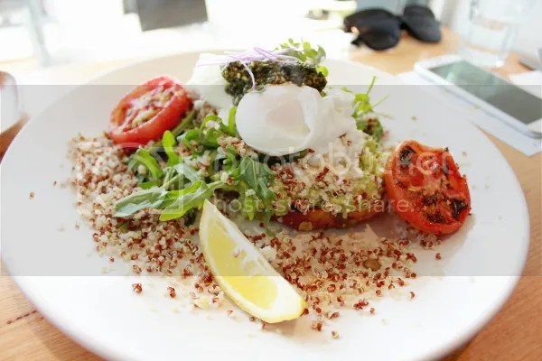 Smashed avocado on pumpkin bread with grilled tomato, crumbled goats cheese, roquette, poached eggs, pesto & sprinkling of quinoa.