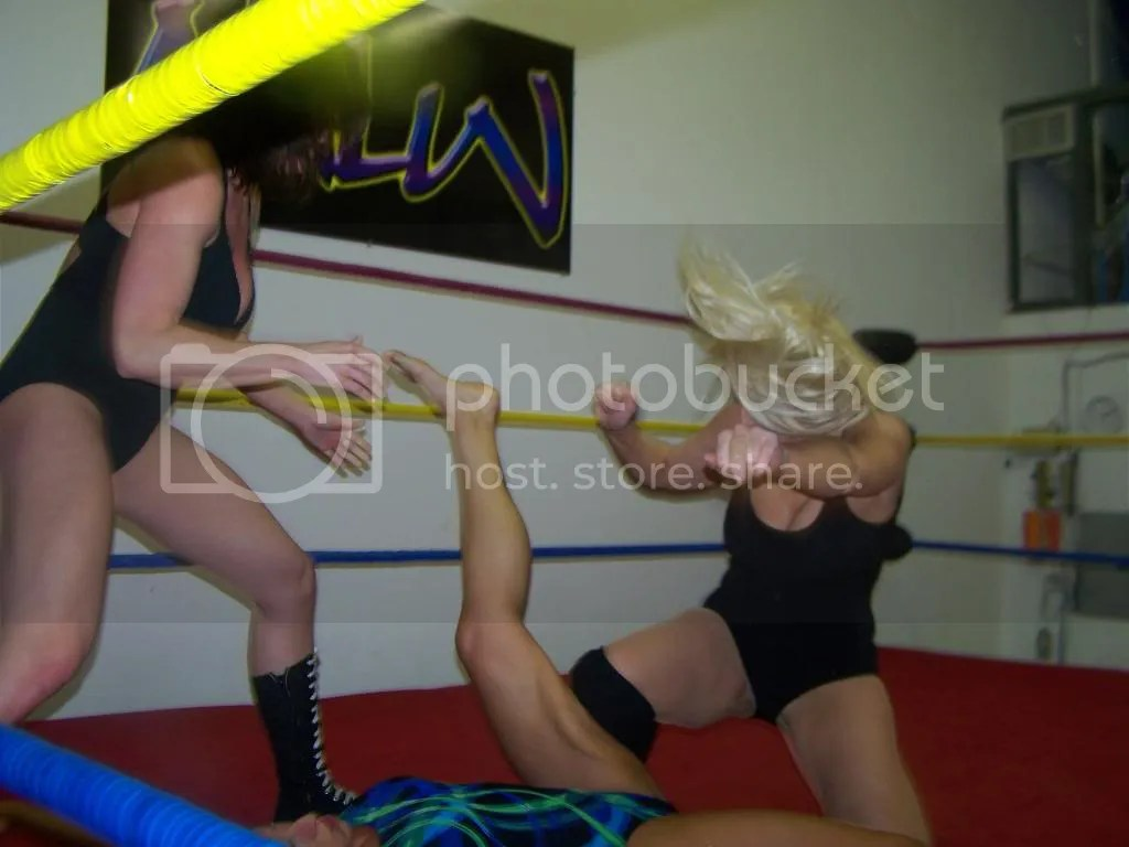 Christie Ricci holds the left foot of Nikki St. John as Amber O' Neal delivers a hard right kneedrop into the back of the left leg of Nikki St. John photo 105_2648.jpg