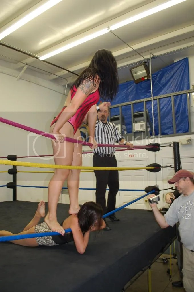 """Smokin' HOTT"" Nikki Lane relentlessly continues standing on the back of Santana Garrett while illegally choking her throat along the bottom ring rope photo DSC_0437.jpg"
