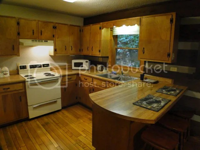 The country kitchen has plenty of cabinet and counter space in this log cabin for sale in Franklin NC