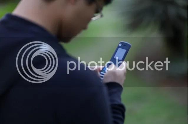 Chico con gafas mirando su móvil