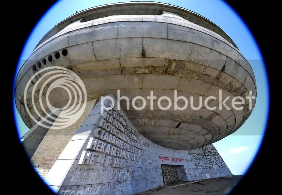 """Напомня """"бетонен венец"""", поставен на самия връх, а 70-метровият пилон е """"развято комунистическо знаме с две рубинени звезди"""", които излъчват червеното сияние на Бузлуджа."""