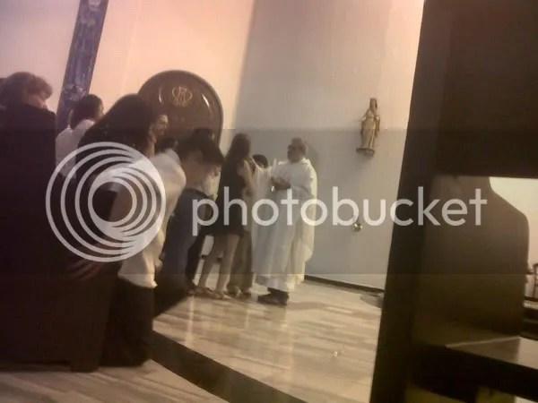 """Raú Lugo Rodríguez da la comunión durante la misa de réquiem por José Rafael Menéndez Navarrete """"Pepín"""" (31 de marzo de 2011)"""