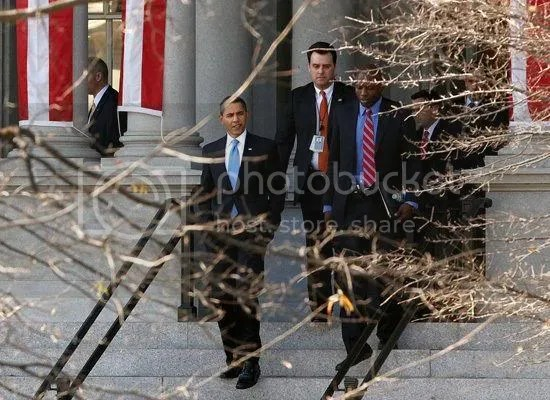 Obama emerges from the Eisenhower Executive Office Building after signing his first five executive orders...
