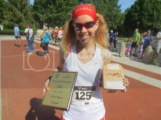Me with my awards for finishing Third Overall Women in the Capital City Stampede 10K (plaque) and for finishing the 2014 Trifecta Series as the First Overall Woman in the Open category.