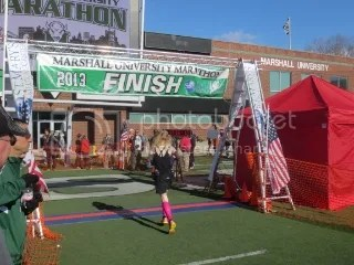 Me crossing the finish line of the Marshall University Marathon carrying a football (which you can't see, but I'm doing it!) - Huntington, West Virginia